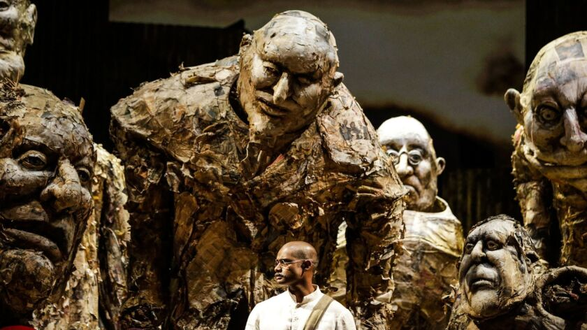 "Sean Panikkar as Gandhi surrounded by puppets of hostile bigwigs incensed by his nonviolent activism in South Africa in Los Angeles Opera's production of ""Satyagraha"" by Philip Glass."