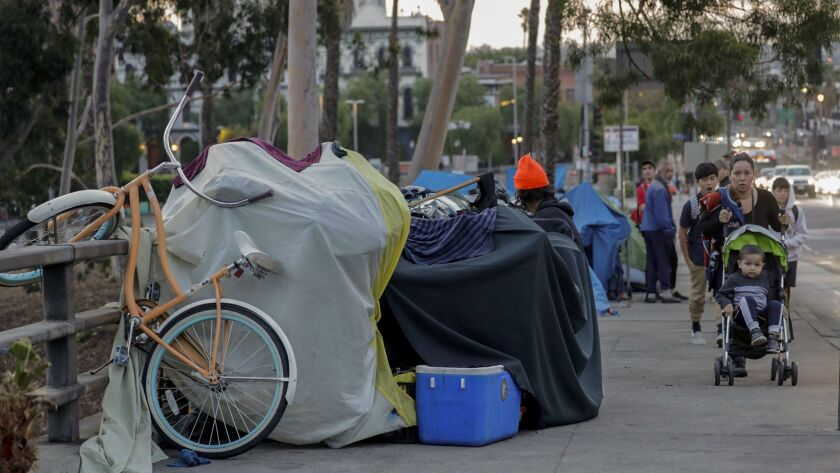Pedestrians share the sidewalk along Arcadia Street with homeless camps in downtown Los Angeles.