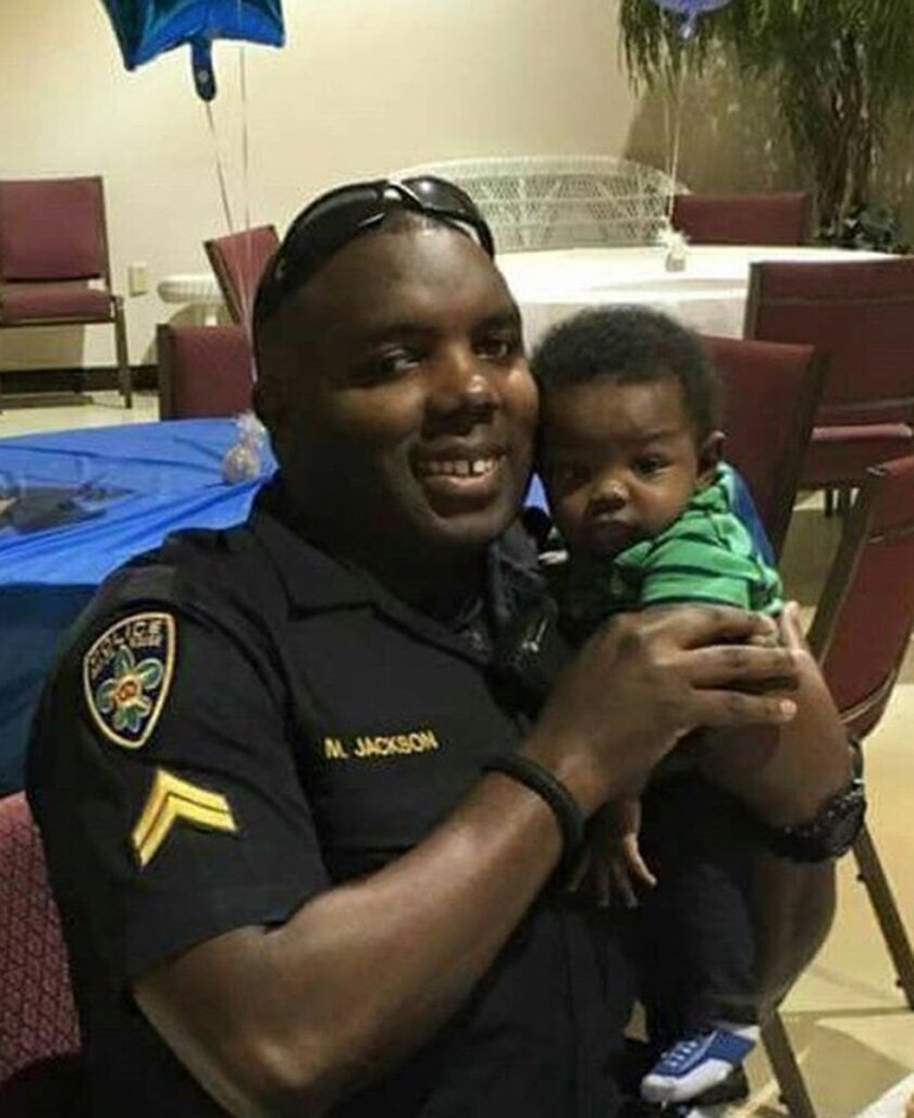 In this 2016 photo provided by Trenisha Jackson, her husband, Baton Rouge Police Officer Montrell Jackson, holds his son Mason at a Father's Day event for police officers in Baton Rouge, La. Montrell Jackson and two other Baton Rouge law enforcement officers investigating a report of a man with an