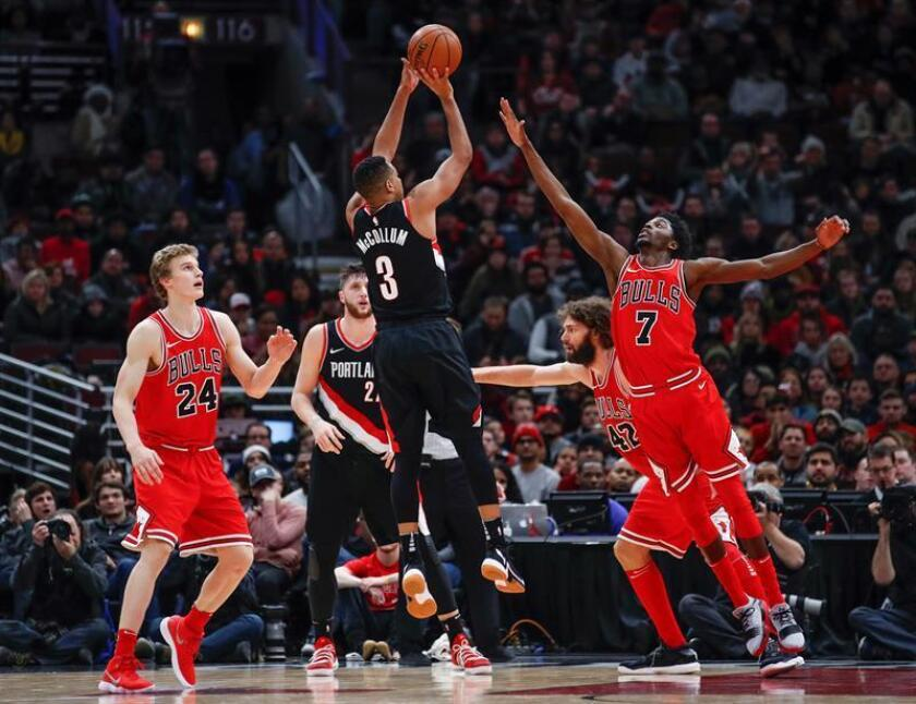 Portland Trail Blazers guard CJ McCollum (C) shoots against Chicago Bulls guard Justin Holiday (R) during overtime of a NBA basketball game. EFE/Archivo