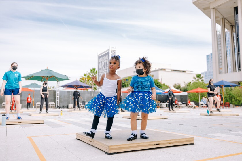 Two young girls in tutus try out their tap-dancing moves on the plaza at the Music Center in downtown L.A.