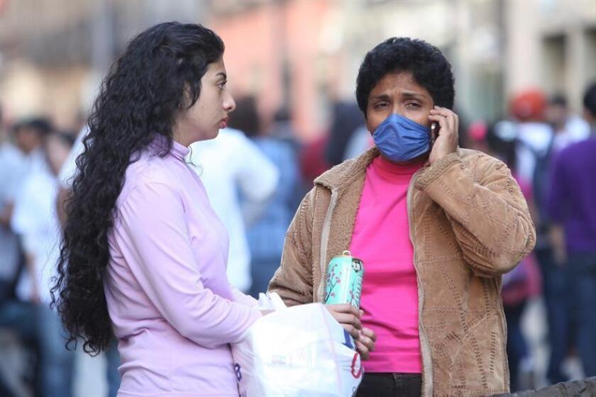 Una mujer utiliza tapabocas mientras camina por una calle en Ciudad de México (México). EFE/Archivo