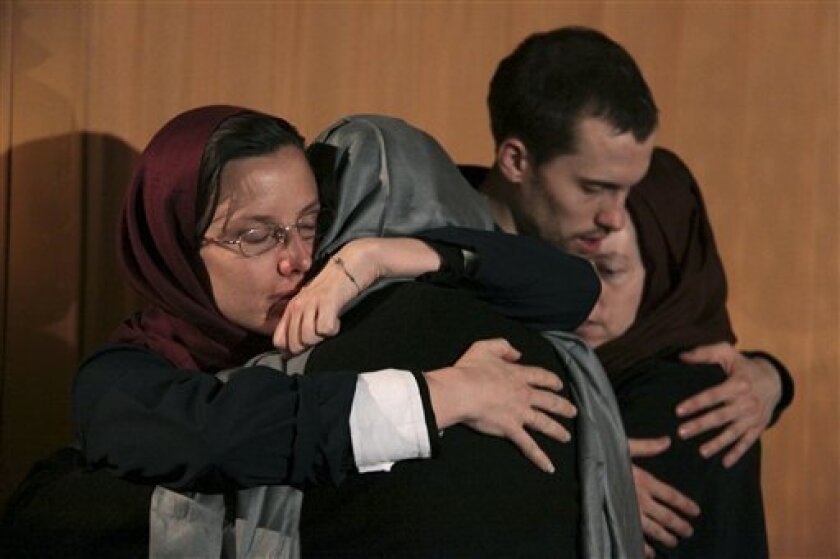 FILE - In this May 21, 2010 file photo, Sarah Shourd, left, hugs her mother Nora Shourd, as Shane Bauer, second right, hugs his mother Cindy Hickey, during their meeting at the Esteghlal hotel in Tehran. Iran announced Thursday that one of the three Americans jailed for more than a year will be released Saturday to mark the end of Islamic holy month of Ramadan. (AP Photo/Press TV, File)
