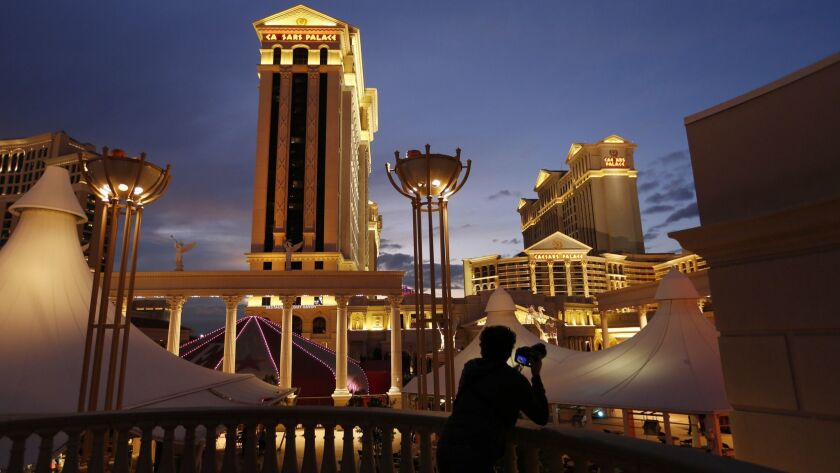 FILE - In this Jan. 12, 2015, file photo, a man takes pictures of Caesars Palace hotel and casino, i