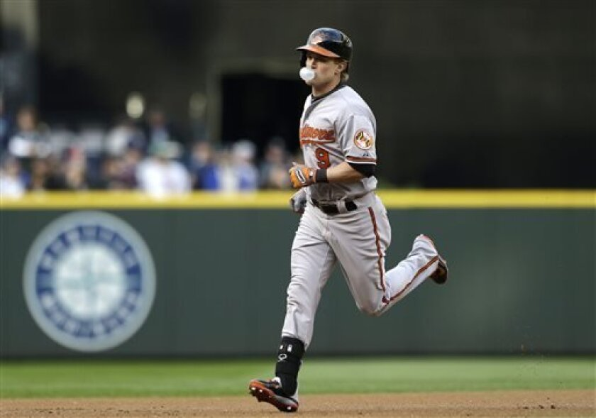 Baltimore Orioles' Nate McLouth blows a bubble as he rounds the bases on a home run against the Seattle Mariners in the first inning of a baseball game Tuesday, April 30, 2013, in Seattle. (AP Photo/Elaine Thompson)