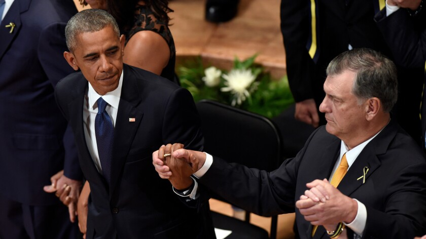 President Barack Obama holds hands with Dallas Mayor Mike Rawlings during an interfaith memorial service for the fallen police officers and members of the Dallas community at the Morton H. Meyerson Symphony Center on July 12.