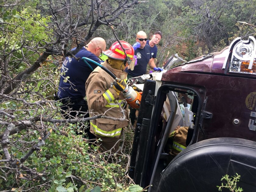 This photo provided by Kim Moore shows firefighters working to extricate a 50-year-old man from his crashed car on Mingus Mountain in Yavapai County, Arizona on Friday, May 27, 2016. Authorities say a man trapped in his crashed vehicle on a central Arizona mountain for three days was rescued thanks