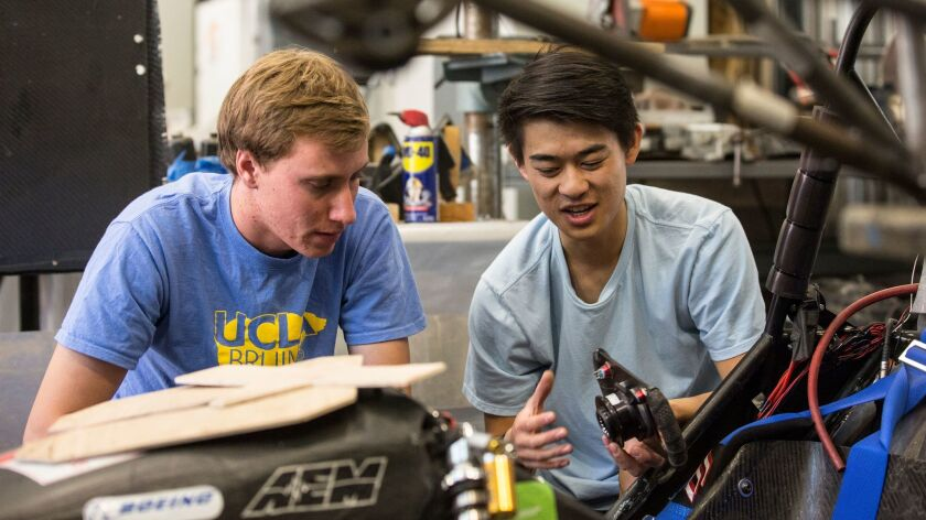UCLA students Brent Kyono, right, and Luke Allee, left, compare parts for UCLA Formula SAE team car