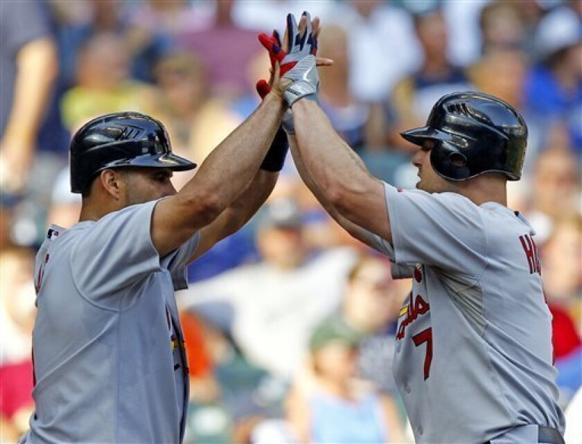 St. Louis Cardinals' Matt Holliday, right, gets a high-five from teammate Albert Pujols after hitting a two-run home run in the fifth inning of a baseball game against the Milwaukee Brewers, Thursday, Sept. 1, 2011, in Milwaukee. (AP Photo/Jeffrey Phelps)