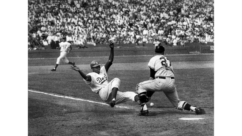 April 18, 1958: The Dodgers' Charlie Neal slides into Giants catcher Bob Schmidt, knocking the ball