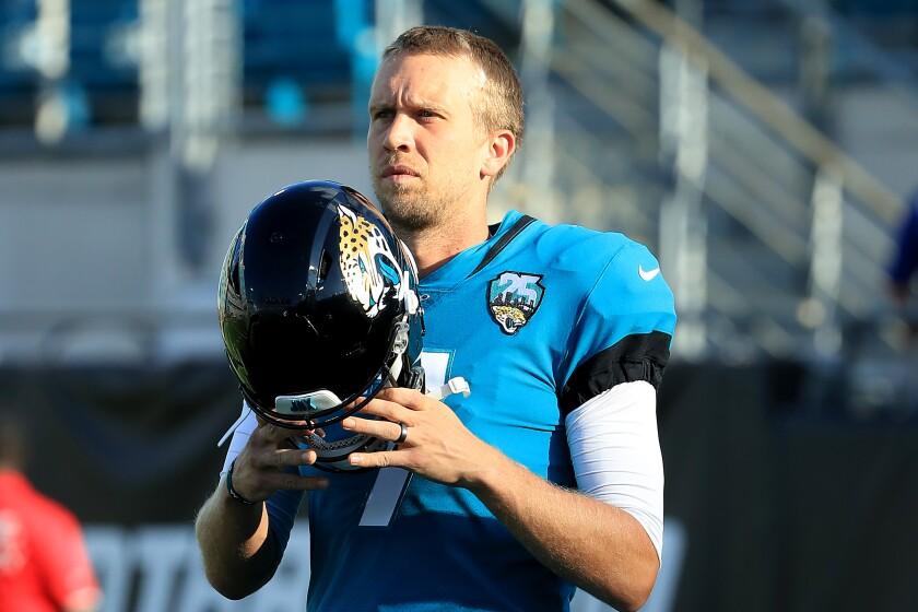 Jacksonville Jaguars quarterback Nick Foles prepares to put on his helmet before a preseason game against the Atlanta Falcons.
