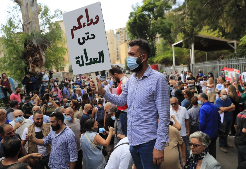 """A protester holds an Arabic placard that reads: """"Behind you until the justice,"""" outside a court building during a demonstration of solidarity with Judge Tarek Bitar who is investigating last year's deadly seaport blast, in Beirut, Lebanon, Wednesday, Sept. 29, 2021. Hundreds of Lebanese, including families of the Beirut port explosion victims, rallied Wednesday outside the court of justice in support of Bitar after he was forced to suspend his work. Bitar is the second judge to take on the complicated investigation.(AP Photo/Hussein Malla)"""