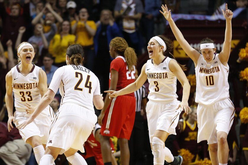 Minnesota guard Carlie Wagner (33), guard Mikayla Bailey (24), guard Shayne Mullaney (3) and center Jessie Edwards (10) celebrate their 90-88 victory against Ohio State in an NCAA college basketball game Wednesday, Feb. 24, 2016 in Minneapolis. (AP Photo/Stacy Bengs)