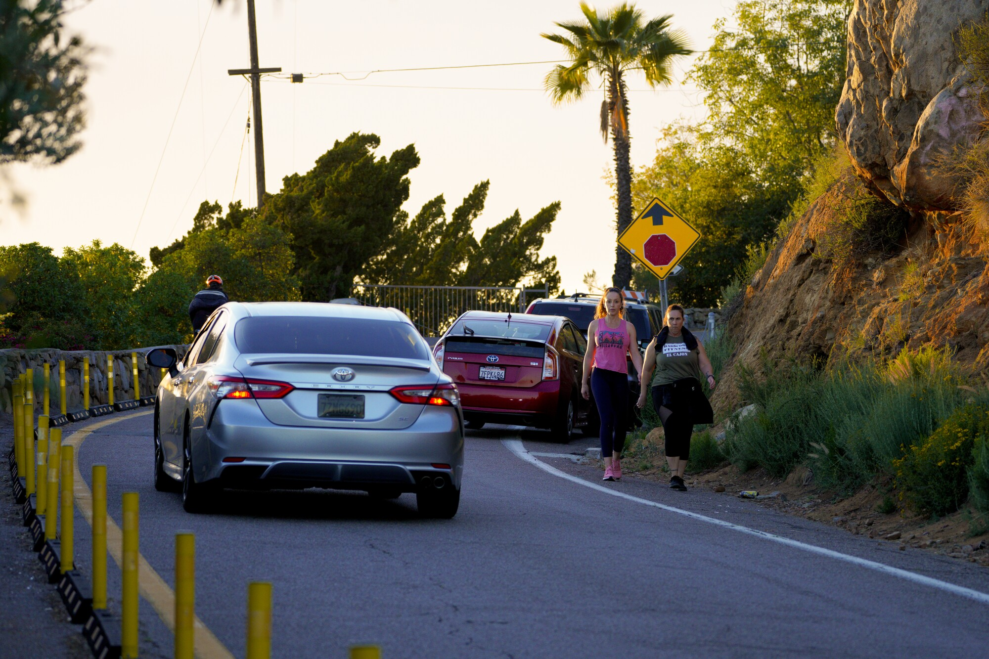 A motorist, a cyclist and pedestrians navigate around several cars illegally parked on Mount Helix Drive.