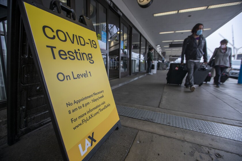 A yellow sign outside airport doors says COVID-19 testing on level 1