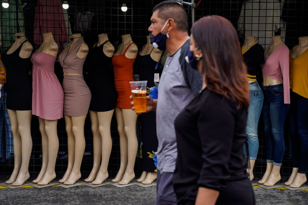 People walk past an open vendor with mannequins displaying clothes at the Santa Fe Springs Swap Meet.