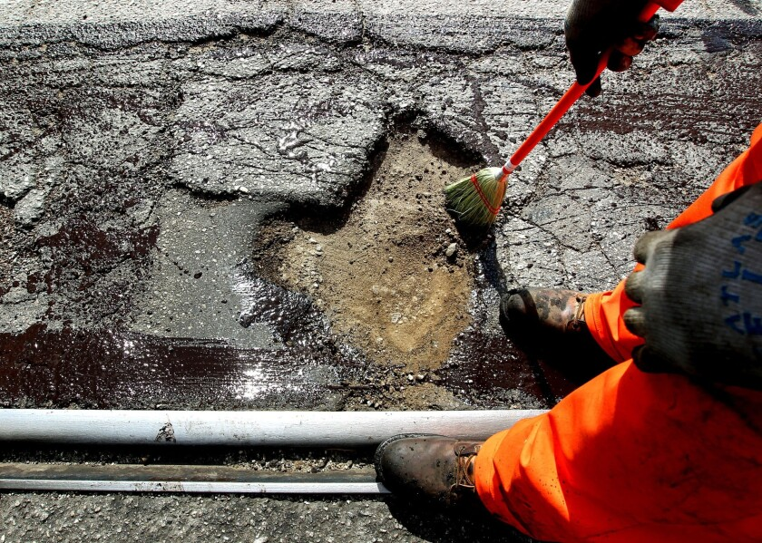 An L.A. Street Services worker prepares to fill a pothole on Alameda Street in June.