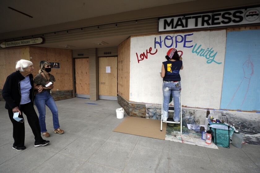 Artist Karla Burner, right, paints a mural on plywood covering the shattered window of a mattress store that was damaged during protests over the death of George Floyd in Minneapolis, Thursday, June 4, 2020, in La Mesa, Calif. California authorities are praising thousands of peaceful protesters who have thronged streets but they also have filed criminal charges against more than 100 people accused of looting and violence. (AP Photo/Gregory Bull)