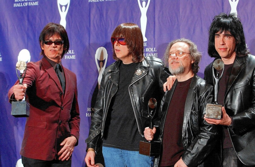 Dee Dee, left, Johnny, Tommy and Marky Ramone hold their awards after being inducted into the Rock and Roll Hall of Fame in 2002. Founding member Joey Ramone died the previous year. Tommy Ramone, the band's original drummer and its last surving member, died Friday at the age of 65.
