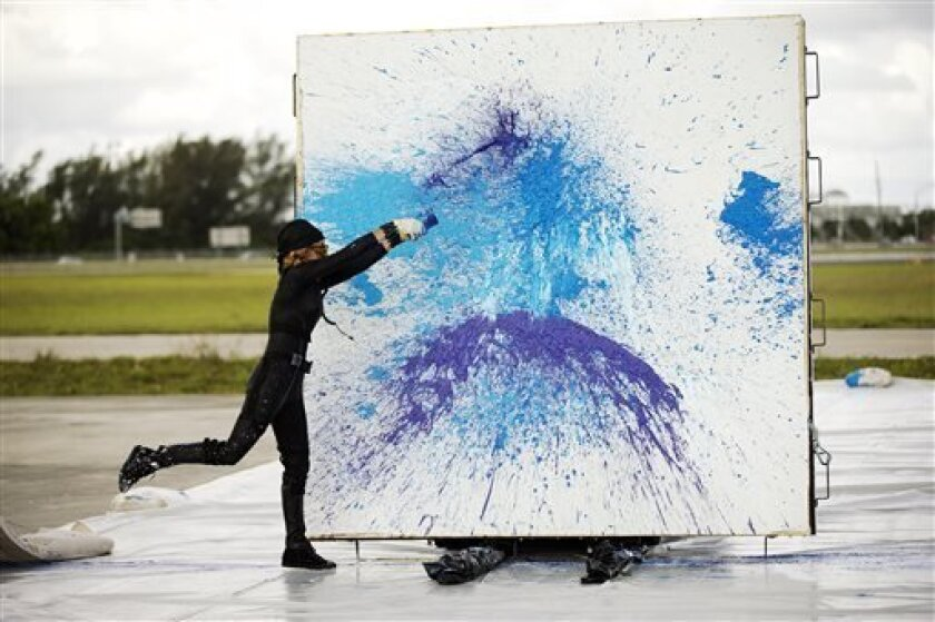 Princess Tarinan von Anhalt works on one of her paintings Tuesday, April 30, 2013 on the West Palm Beach, Fla. airport tarmac. Princess Tarinan von Anhalt's creative process involves hurling paint into a Learjet engine, splattering the colors onto a canvas to create the abstract designs for which s