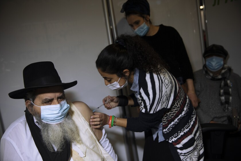A man receives a coronavirus shot from medical staff at a COVID-19 vaccination center in Jerusalem on Monday.