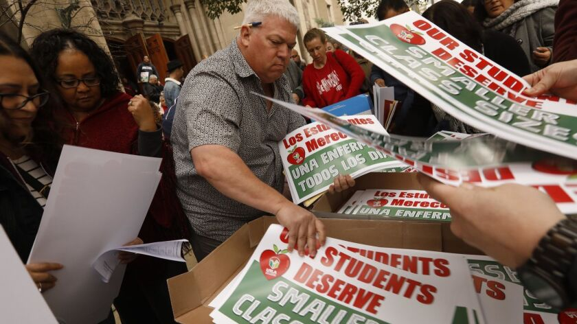 Members of United Teachers Los Angeles pick up signs and other materials Saturday for a possible upcoming strike after a meeting at the Immanuel Presbyterian Church in Los Angeles.
