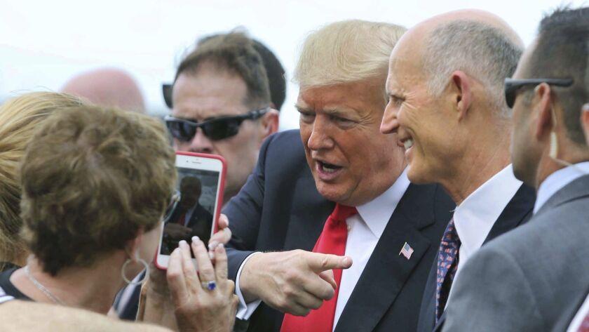 Florida Gov. Rick Scott, right, welcomes President Trump at Orlando International Airport on Monday. Scott is challenging U.S. Sen. Bill Nelson in next month's election.