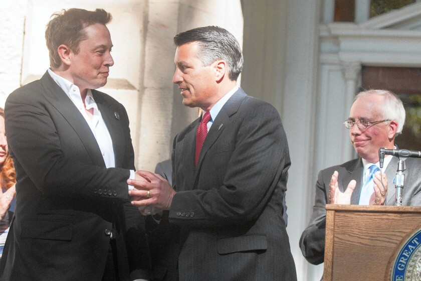 Elon Musk, left, CEO of Tesla Motors, appears at a news conference with Nevada Gov. Brian Sandoval.