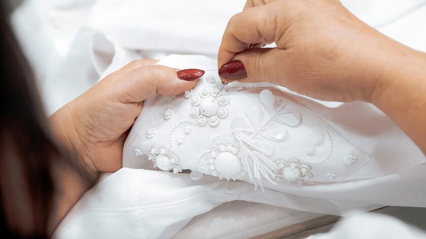 A Valentino seamstress adds custom embellishment to a shirt sleeve.