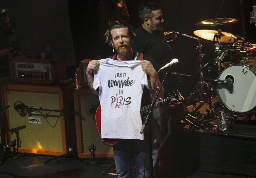 """Frontman of California, USA, rock band Eagles of Death Metal, Jesse Hughes holds a T-shirt with slogan, """"I really wanna'be in Paris"""" as the rock band performs Tuesday Feb. 16, 2016, at the Olympia concert hall in Paris, France.  The band performed Tuesday at a highly charged Paris concert filled wi"""
