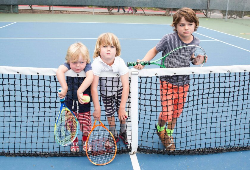 Archie, Barnaby and Harry Pearce, sons of La Jolla YMCA member Victoria Pearce, pose on a tennis court at La Jolla YMCA. The tennis courts will be demolished in August. Victoria and other members say they weren't notified about the decision until a tennis instructor informed them last week.