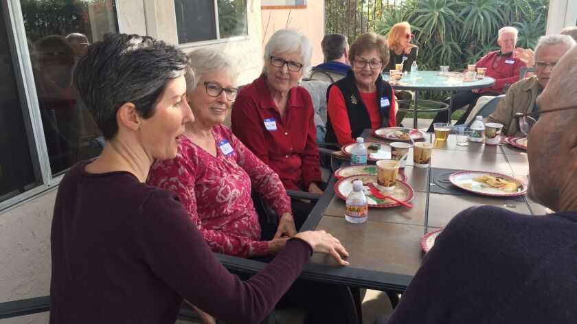 Tremble Clefs director Kathleen Hansen, left, with members of the North County choir at their annual holiday party last week in Carlsbad.