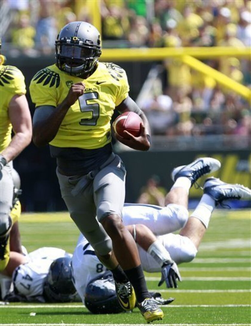 Oregon quarterback Darron Thomas (5) carries the ball in the first quarter of an NCAA football game against Nevada on Saturday, Sept. 10, 2011, in Eugene, Ore. (AP Photo/Rick Bowmer)