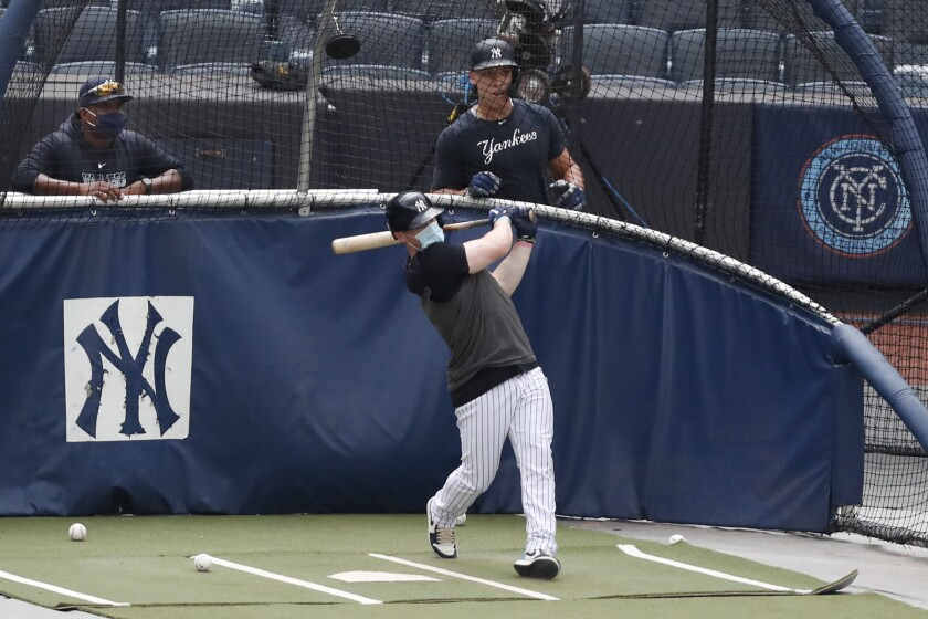 New York Yankees hitting coach Marcus Thames, left, and Aaron Judge, right, watch Clint Frazier bat in the cage during a summer training camp workout, Wednesday, July 8, 2020, at Yankee Stadium in New York. (AP Photo/Kathy Willens)