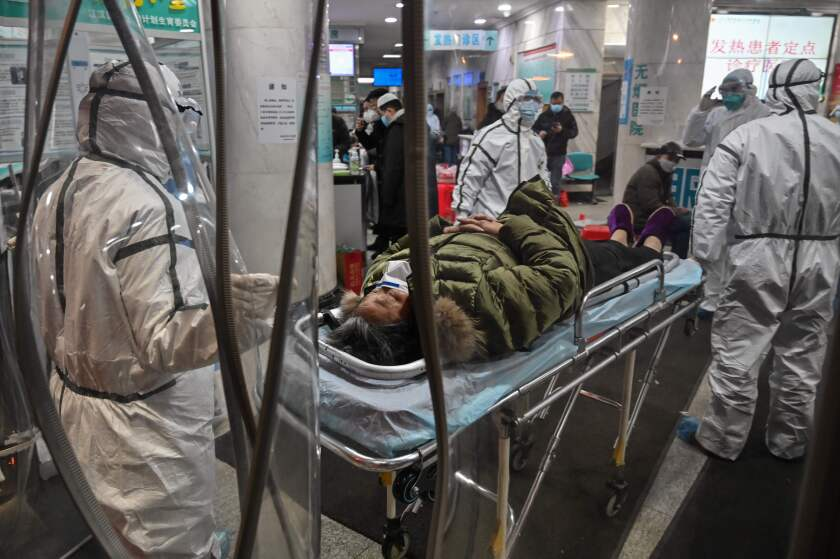 Medical staff  arrive with a patient at the Wuhan Red Cross Hospital in Wuhan. The Chinese army deployed medical specialists to the epicenter of the coronavirus viral outbreak.