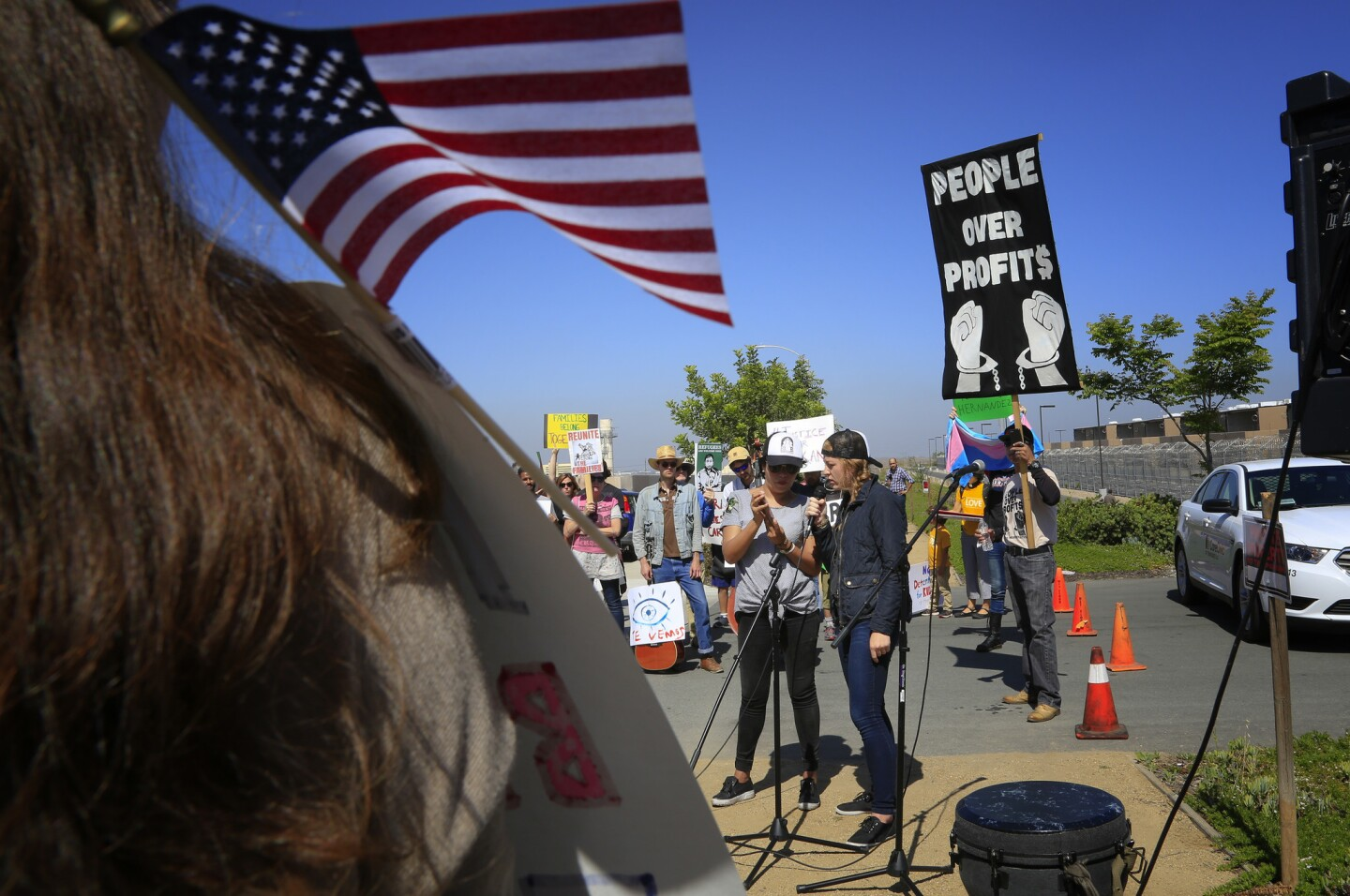 Speakers took turn speaking to the crowd of supporters during the protest rally near the entrance to the Otay Mesa Detention Center.