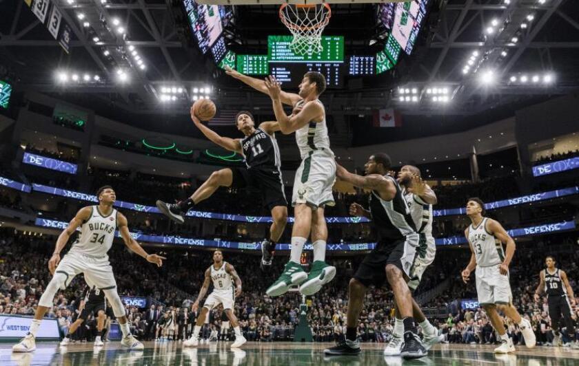 El jugador de San Antonio Spurs Bryn Forbes (i) intenta encestar ante la oposición del jugador de Milwaukee Bucks Brook Lopez (c), hoy. EFE