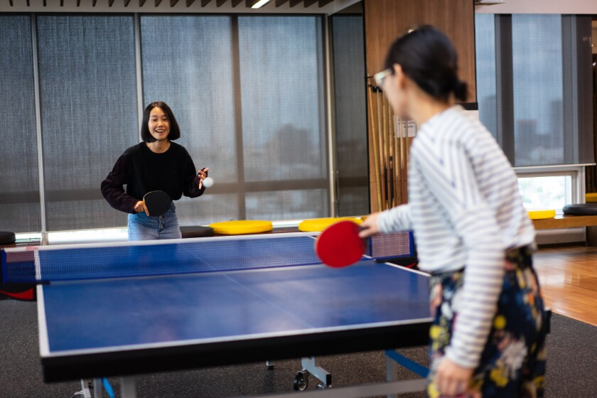 Girls is playing table tennis at the office.