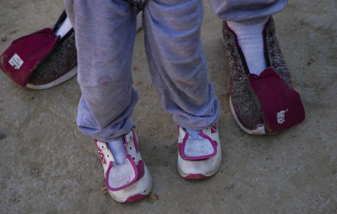 Shoes on asylum seekers' feet have no shoelaces.