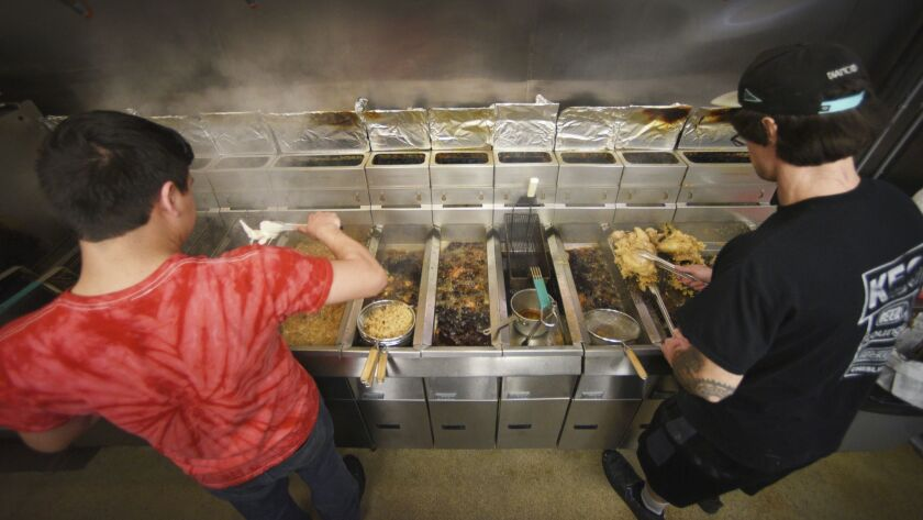 In a Tuesday, Dec. 4, 2018 photo, Cooks Jake Kongi, left, and Brian Scott, right, fry more chicken f