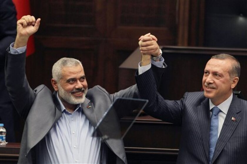 FILE - In this Jan. 3, 2012 file photo, Turkey's Prime Minister Recep Tayyip Erdogan, right, and the Gaza Strip's Hamas premier Ismail Haniyeh salute lawmakers and supporters of Erdogan's Islamic-rooted Justice and Development Party at the Parliament in Ankara, Turkey. Ties between Turkey, NATO's biggest Muslim member, and Hamas, the Islamic militant group that says Israel should not exist, are blossoming. Last month, the Hamas premier visited the Turkish prime minister at his Istanbul home. Today, Turkish and Palestinian flags fly side by side at a building site in the Hamas-controlled Gaza Strip. (AP Photo/File)