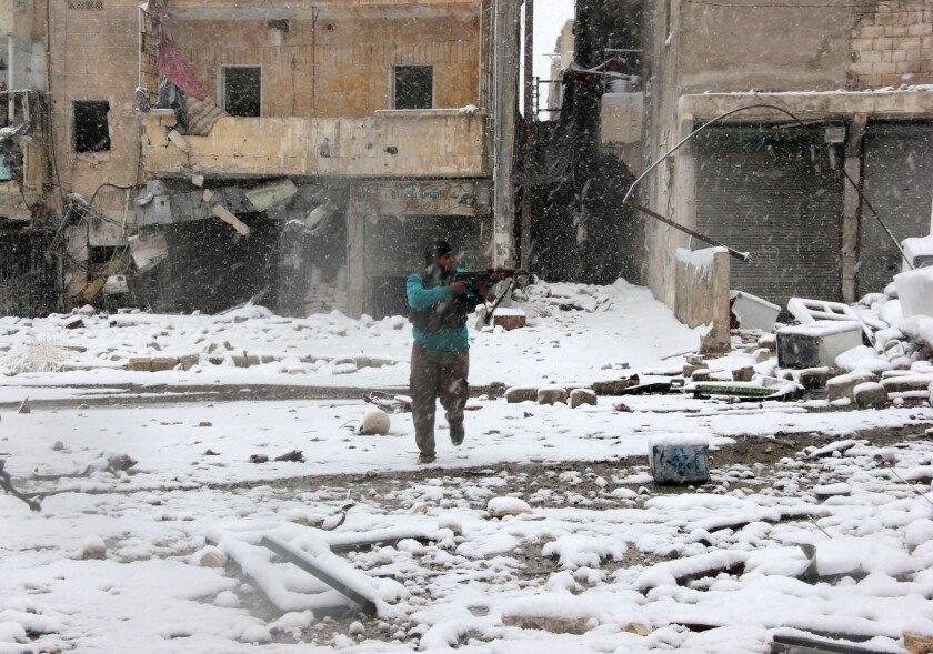 A Syrian rebel aims his weapon as he stands amid snow during clashes with pro-government forces in the Salaheddin neighborhood of Aleppo.