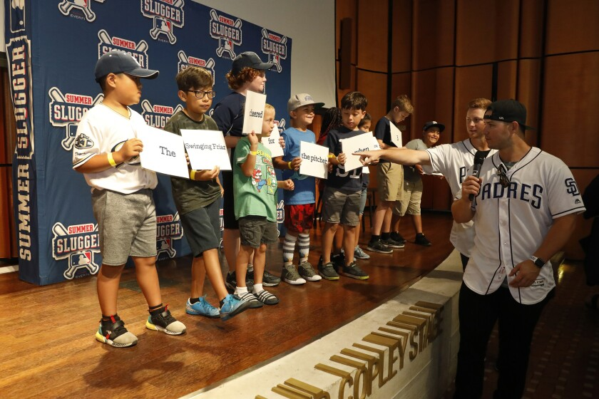 Padres players Ty France (foreground right) and Eric Lauer arrange student volunteers holding cards into a complete sentence at the San Diego Central Library on Saturday morning. The players' appearance was part of an event celebrating the students from ages 8 to 11 who participated in Summer Slugger, a baseball-themed digital learning course.