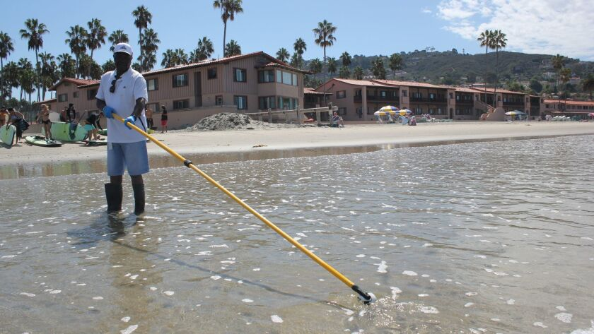 San Diego County environmental health technician Daniel Collins obtains a water sample from La Jolla Shores.