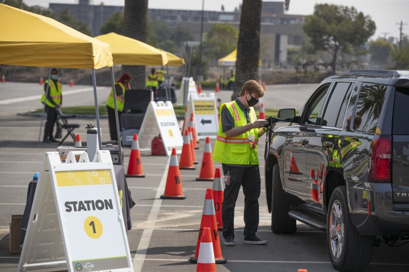 An Orange County election services worker demonstrates drive-through voting at the Honda Center in Anaheim on Sept.16.