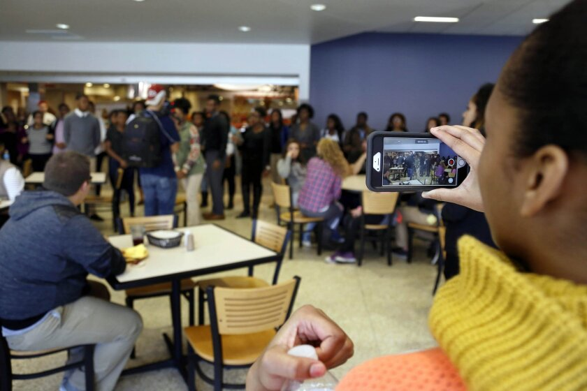 In this Saturday, Nov. 7, 2015, photo, a member of Concerned Student 1950 films a protest in Mark Twain Dining Hall on University of Missouri campus, in Columbia, Mo. Some campus groups have been protesting the way university president Tim Wolfe has dealt with issues of racial harassment during the