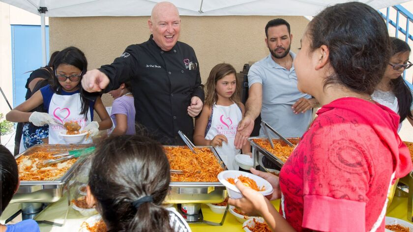 Chef Bruno Serato, top left, serves pasta to children Tuesday at the Boys and Girls Club on the Golden West College campus in Huntington Beach. Serato's nonprofit will now be giving food to children at the club.