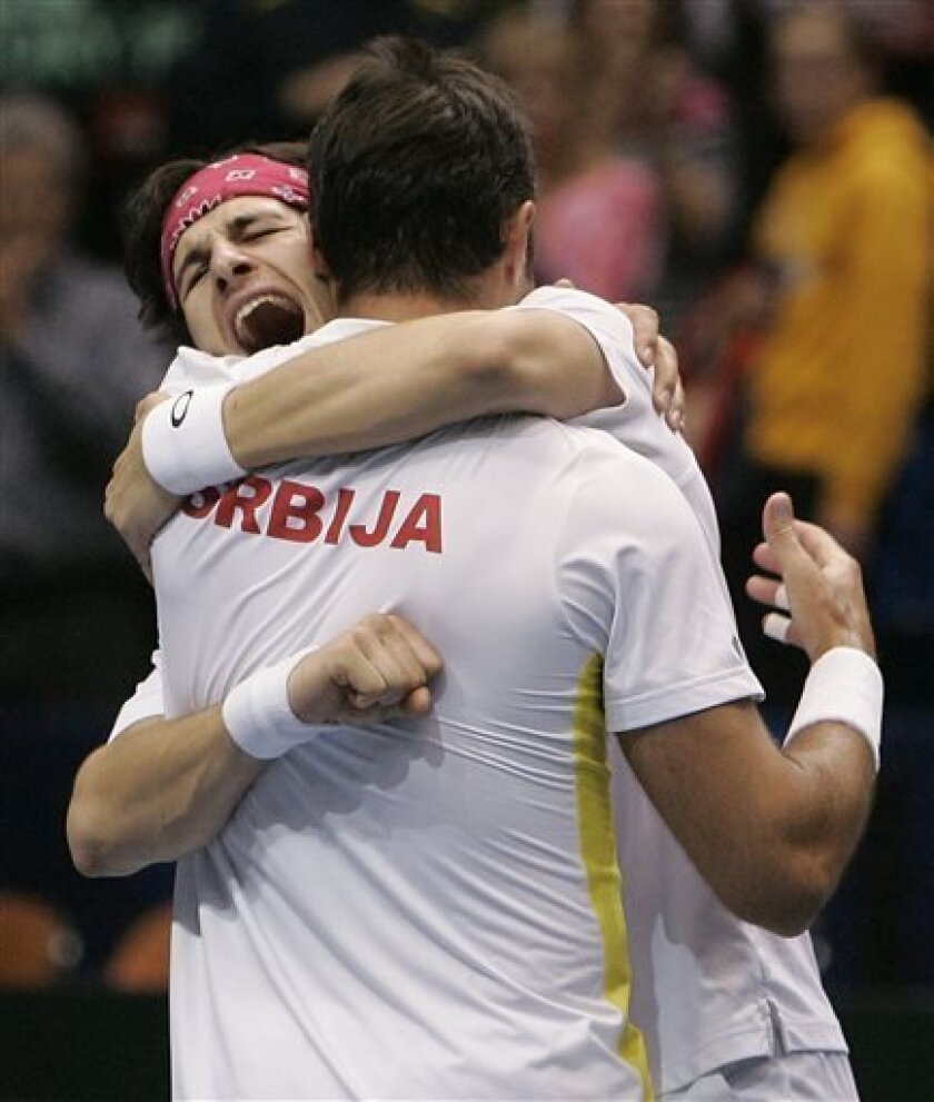 Serbia's Ilija Bozoljac, facing camera, and Nenad Zimonjic celebrate after defeating Bob Bryan and Mike Bryan in the doubles match during the Davis Cup tennis tournament Saturday, April 6, 2013, in Boise, Idaho. The Serbian team won 7-6 (5), 7-6 (1), 5-7, 4-6, 15-13. (AP Photo/Matt Cilley)