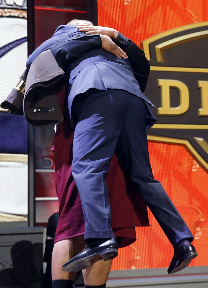 Washington defensive lineman Danny Shelton picks up NFL commissioner Roger Goodell as he celebrates after being selected by the Cleveland Browns as the 12th pick in the first round of the 2015 NFL Draft,  Thursday, April 30, 2015, in Chicago. (AP Photo/Charles Rex Arbogast)