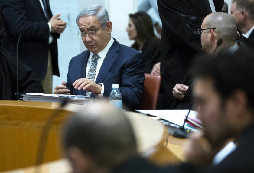 Israeli Prime Minister Benjamin Netanyahu, center left, and unidentified defense lawyers wait for the Supreme Court to convene, in Jerusalem, Sunday, Feb. 14, 2016. Netanyahu made an unprecedented appearance at the Supreme Court to defend a deal signed in December with U.S. and Israeli developers d